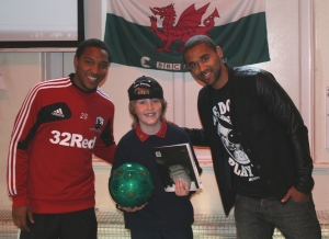 Daniel Russell recieves his autographed football from Luke and Jonathan